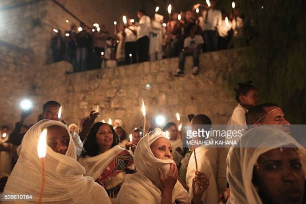TOPSHOT Ethiopian Christian pilgrims hold candles during an Ethiopian Orthodox ceremony of the Holy Fire at the Dir AlSultan Church held on the roof...