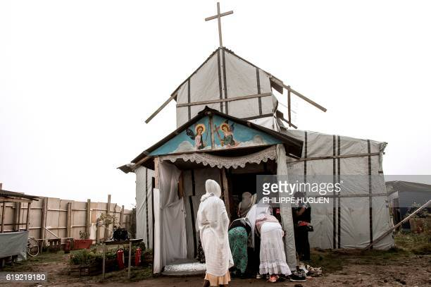 TOPSHOT Ethiopian Coptic migrants arrive for a mass at the makeshift Orthodox church in the Jungle' migrant camp on October 30 2016 in Calais...