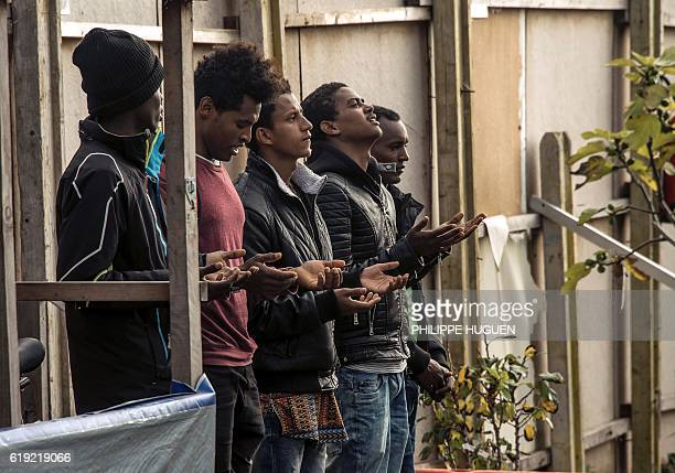 Ethiopian Coptic migrants pray as they arrive for a mass at the makeshift Orthodox church in the Jungle' migrant camp on October 30 2016 in Calais...