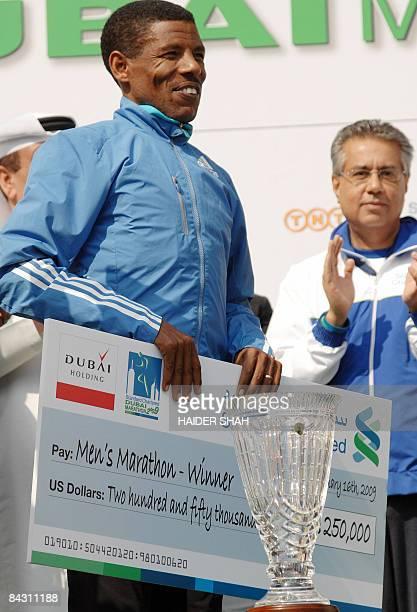 Ethiopian Haile Gebrselassie holds his prize money after winning the Dubai Marathon 2009 the world's richest marathon in the Gulf emirate on January...