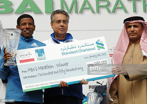 Ethiopian Haile Gebrselassie poses with his trophy and prize money after receiving them from Emirati vice president of the executive sports committee...