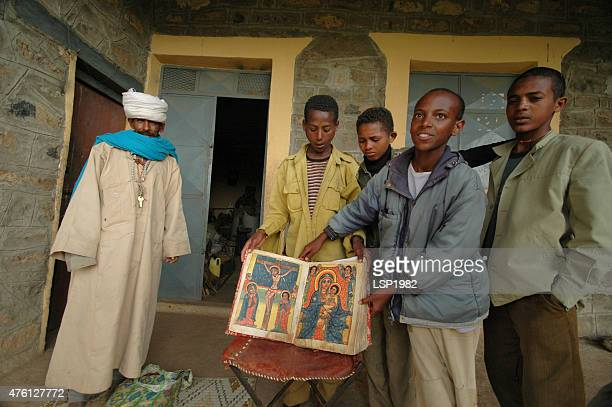 ethiopian kids and priest showing old bible. - axum stock photos and pictures