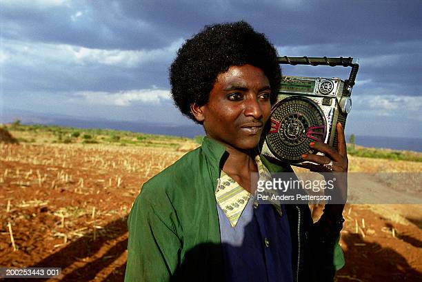ethiopian man carries radio in erer valley in rural eastern, ethiopia - per-anders pettersson stock pictures, royalty-free photos & images