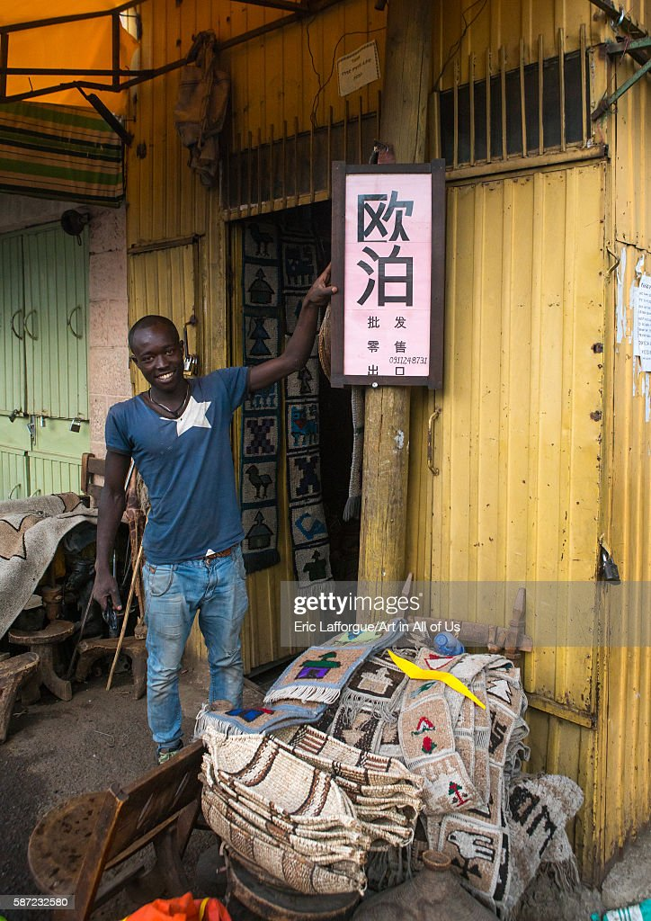 Ethiopian man in front of a billboard in chinese language to sell opales, Addis abeba region, Addis ababa, Ethiopia : News Photo