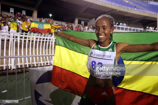 Ethiopian Meseret Defar holds her national flag as she celebrates her gold medal 18 July 2007 in the Women's 5000 final at the 9th AllAfricanGames...