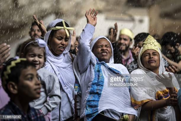 Ethiopian Orthodox and Egyptian Coptic Christians react after being sprayed by holy water by a priest as they take part in Palm Sunday celebrations...