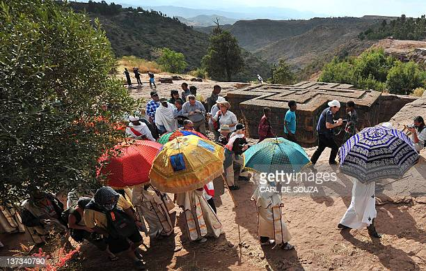 Ethiopian Orthodox Christian priests and monks walk past the rockhewn church Bete Giyorgis as tourists look on during the annual festival of Timkat...