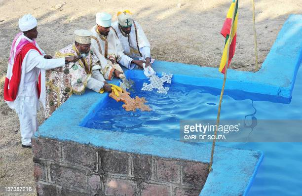 Ethiopian Orthodox Christian priests bless a cross shaped pool of water during the annual festival of Timkat in Lalibela Ethiopia which celebrates...