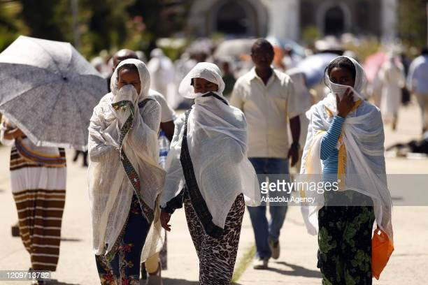 Ethiopian Orthodox Christian women cover their faces as a preventive measure against the coronavirus pandemic while making their way to attend the...