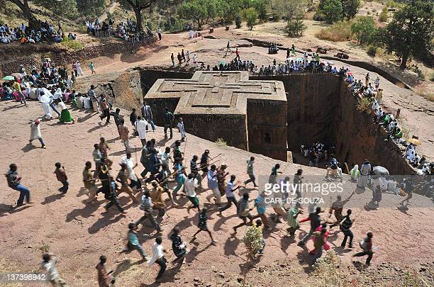 Ethiopian Orthodox Christians dance near to the rockhewn church Bete Giyorgis during the annual festival of Timkat in Lalibela Ethiopia which...