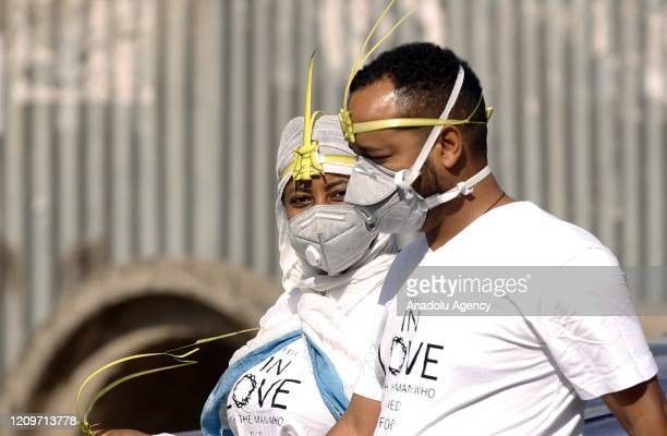 Ethiopian Orthodox Christians wearing leaf crowns made out of date palm and face masks as a preventive measure against the coronavirus pandemic make...