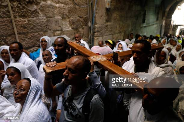 Ethiopian Orthodox pilgrims carry a wooden cross along the Via Dolorosa during the Orthodox Good Friday procession in Jerusalem's Old City on April 6...