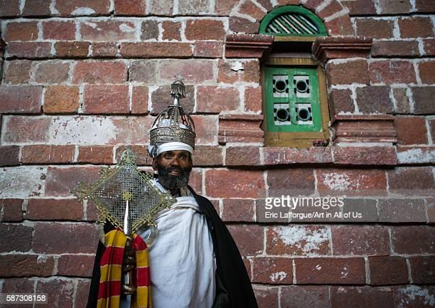 Ethiopian orthodox priest holding a cross inside nakuto lab rock church amhara region lalibela Ethiopia on February 23 2016 in Lalibela Ethiopia