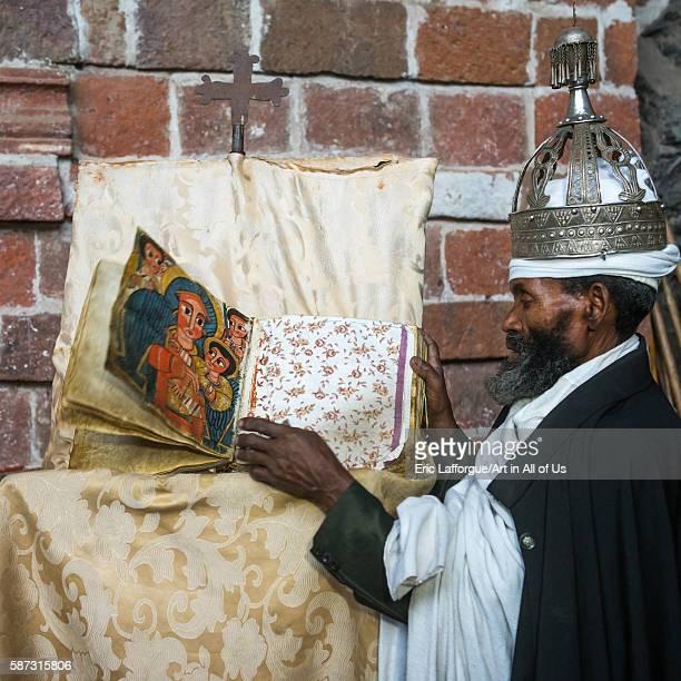 Ethiopian orthodox priest with an old bible in nakuto lab rock church amhara region lalibela Ethiopia on February 23 2016 in Lalibela Ethiopia