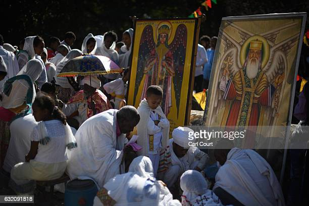 Ethiopian Orthodox worshippers chat around religious paintings during the annual Timkat Epiphany celebration on January 19 2017 in Gondar Ethiopia...