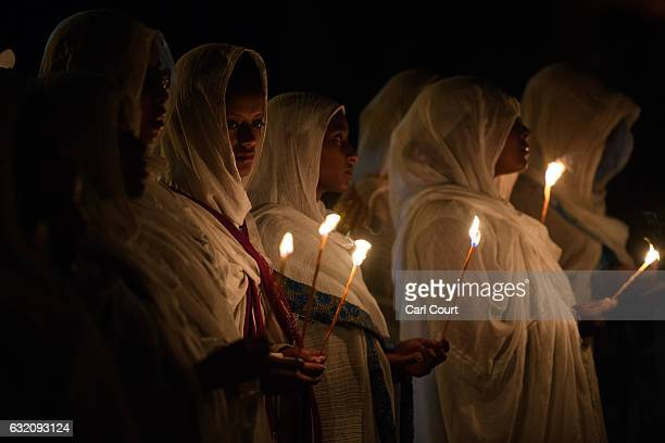 Ethiopian Orthodox worshippers hold candles as they pray at Fasilides Bath during the annual Timkat Epiphany celebration on January 19 2017 in Gondar...