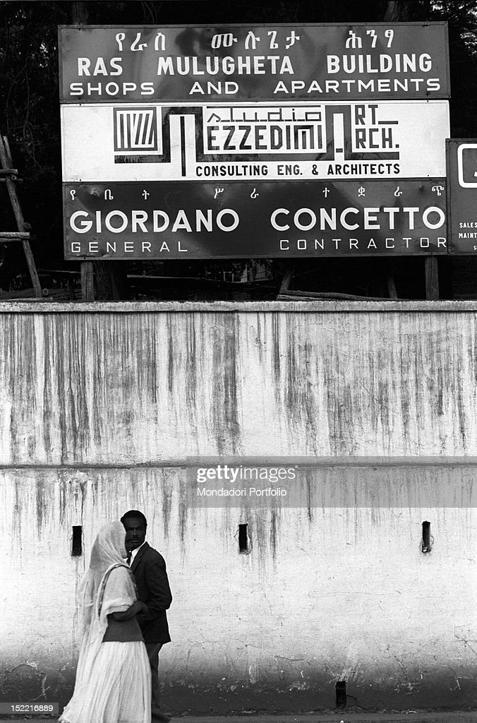Ethiopian people walking near the building site of Giordano Concetto's company. Many Italian building firms are operating in the city. Addis Ababa, November 1966