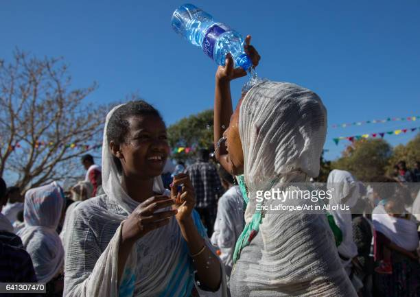 Ethiopian pilgrim woman putting some holy water on her face during Timkat epiphany festival on January 19 2017 in Lalibela Ethiopia