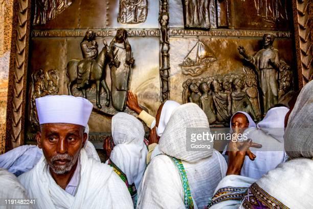 Ethiopian pilgrims touching the main door of the Annunciation Roman catholic basilica, Nazareth, Galilee, Israel.