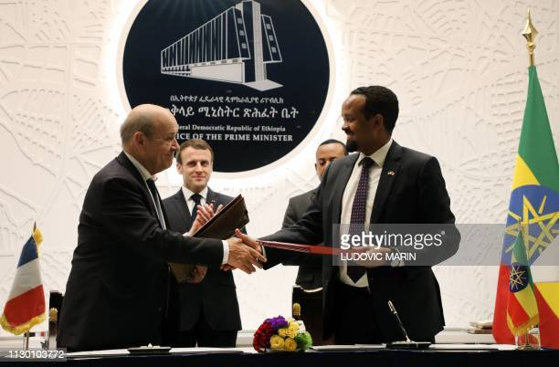 Ethiopian Prime Minister Abiy Ahmed and French President Emmanuel Macron applaud while French Foreign Minister JeanYves Le Drian and Ethiopian...