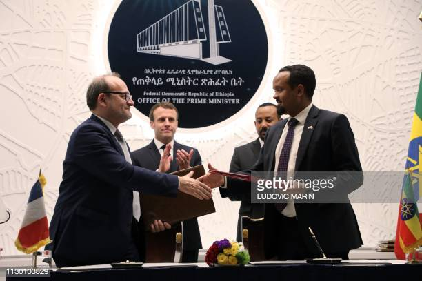 Ethiopian Prime Minister Abiy Ahmed and French President Emmanuel Macron applaud while AFD Managing Director Remy Rioux and Ethiopian Finance...