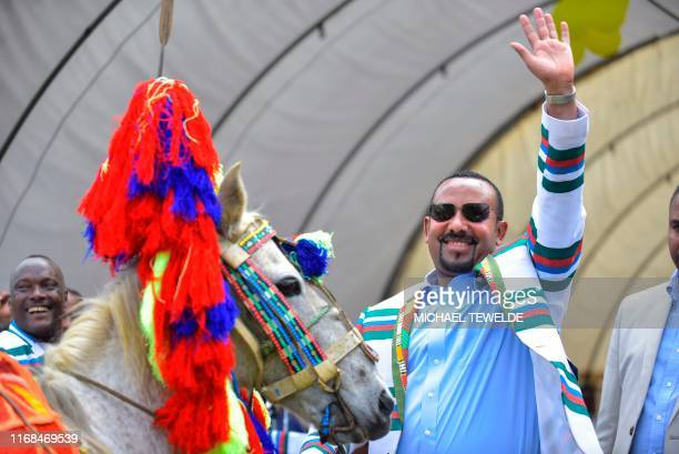 Ethiopian Prime Minister Abiy Ahmed gestures after receiving a horse as a gift from the elders of the Kafficho ethnic group during a visit to Bonga,...