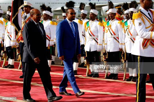 Ethiopian Prime Minister Abiy Ahmed reviews the honour guard with Sudanese President Omar alBashir following his arrival in Khartoum for an official...