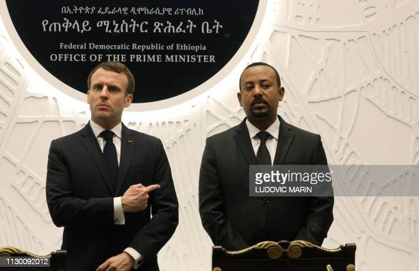 Ethiopian Prime Minister Abiy Ahmed speaks with French President Emmanuel Macron after signing agreements during a meeting on March 12 2019 in Addis...