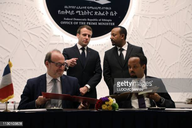 Ethiopian Prime Minister Abiy Ahmed speaks with French President Emmanuel Macron while AFD Managing Director Remy Rioux and Ethiopian Finance...