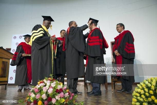 Ethiopian Prime Minister Hailemariam Desalegn places a cap on the head of Bill Gates cochair of Bill and Melinda Gates Foundation during a ceremony...