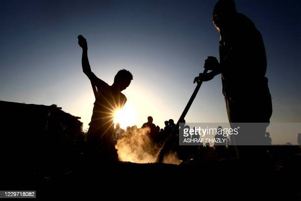 Ethiopian refugees who fled fighting in Tigray province cook food for others at the Um Raquba camp in Sudan's eastern Gedaref state, on November 21,...