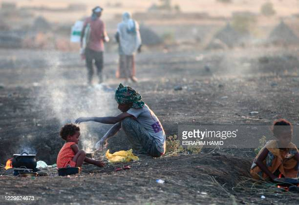 Ethiopian refugees who fled intense fighting in their homeland of Tigray, cook their meal in the border reception centre of Hamdiyet, in the eastern...