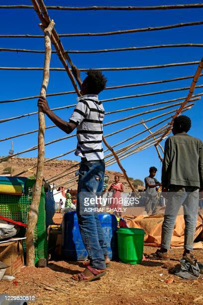 Ethiopian refugees who fled the Tigray conflict, build temporary huts at Um Raquba camp in Sudan's eastern Gedaref province on November 28, 2020. -...