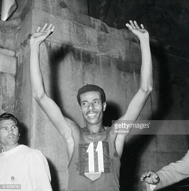 Ethiopian runner Abebe Bikila waves to the cheering crowd and photographers after he won the Olympic Marathon in a time of about 2 hours 15 minutes...