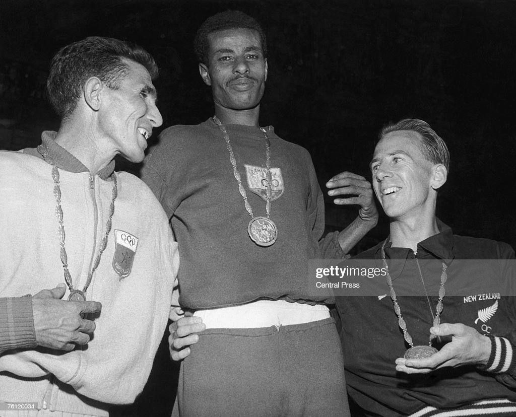 Ethiopian runner Bikila Abebe with his gold medal after winning the marathon at the 1960 Olympics in Rome, 12th September 1960. Abdeslon Rhadi of Morocco, left, won silver and Barry Magee of New Zealand won the bronze. Abebe, one of Haile Selassie's personal bodyguards, ran the race barefoot and set an Olympic record with his victory.
