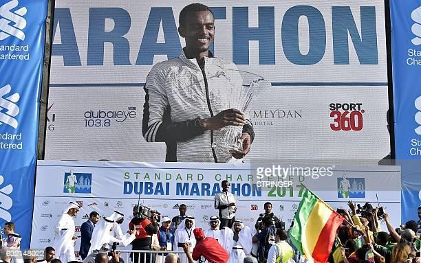 Ethiopian runner Tamirat Tola celebrates on the podium after winning the men's marathon in Dubai on January 20 2017 Middle distance legend Kenenisa...