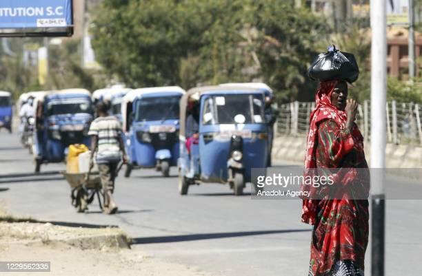 Ethiopian woman carrying a package on her head is seen as Tuk-Tuks are seen behind in Jigiiga capital of Somali region, Ethiopia on November 03, 2020