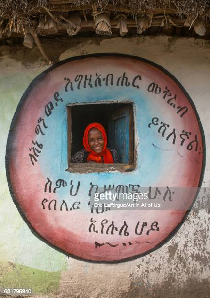 Ethiopian woman standing in the window of her traditional painted house Kembata Alaba Kuito Ethiopia on March 8 2016 in Alaba Kuito Ethiopia