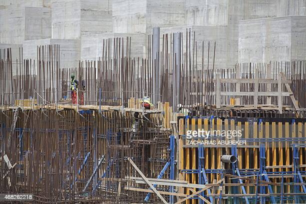 Ethiopian workers stand on scaffolding on March 31 2015 during the construction of the Grand Renaissance Dam near the SudaneseEthiopian border...