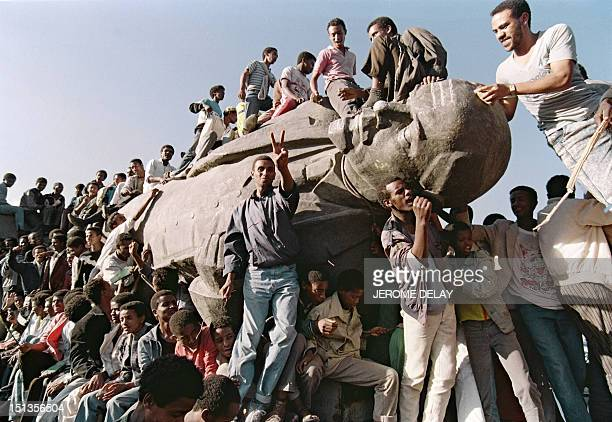 Ethiopian youths chant as they stand on the toppled statue sculptured in a pure style of socialist realism of Russian Bolshevik revolutionary leader...