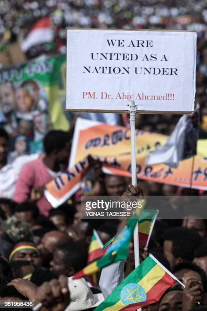Ethiopians hold a placard and flags as they gather in Meskel Square in Addis Ababa on June 23 for a rally called by the Prime Minister Abiy Ahmed A...