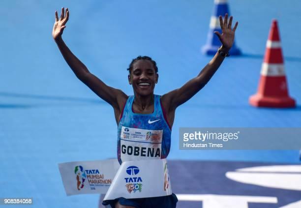 Ethiopia's Amane Gobena celebrates as she prepares to cross the finish line to win the women's category of the Tata Mumbai Marathon 2018 at CSMT on...