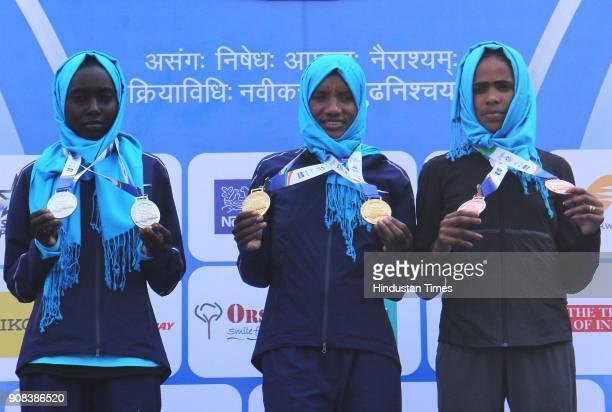 Ethiopia's Amane Gobena who won the women's category of Mumbai Marathon poses with second position Bornes Kitur of Kenya and third position Shuko...