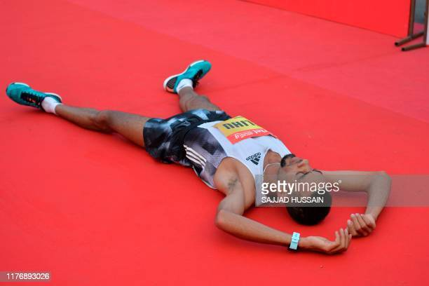 Ethiopia's Andamlak Belihu lies on the ground after crossing the finish line to win the men's title of the 2019 Delhi half marathon in New Delhi on...