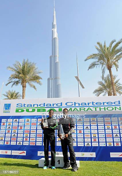 Ethiopia's Aselefech Mergia Medessa and her compatriot Ayele Abshero pose with their trophies after winning the women's and the men's Dubai Marathon...