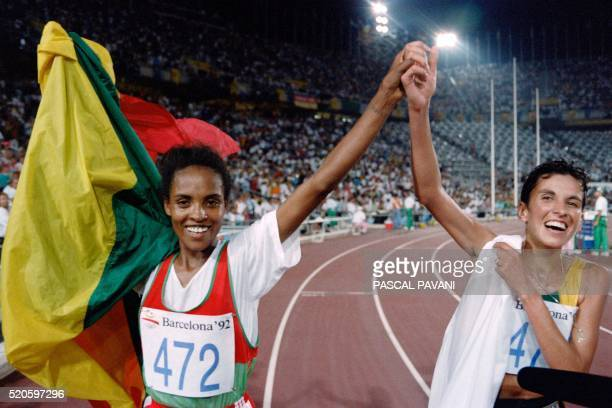 Ethiopia's Derartu Tulu and Elana Meyer of South Africa join hands in a victory lap after the women's 10000m final at the athletics event during the...