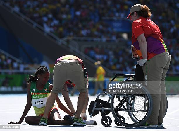 TOPSHOT Ethiopia's Etenesh Diro is helped by officials after she competed in the Women's 3000m Steeplechase Round 1 during the athletics event at the...