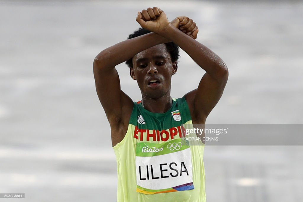 TOPSHOT - Ethiopia's Feyisa Lilesa (silver) crosses the finish line of the Men's Marathon athletics event during the Rio 2016 Olympic Games at the Sambodromo in Rio de Janeiro on August 21, 2016. Lilesa crossed his arms above his head as he finished the race as a protest against the Ethiopian government's crackdown on political dissent. / AFP / Adrian DENNIS