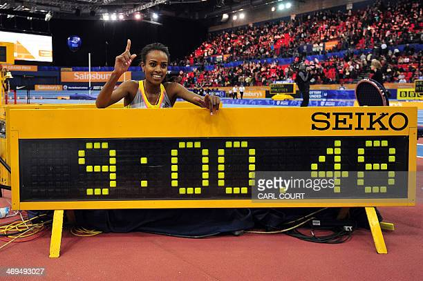 Ethiopia's Genzebe Dibaba poses for photographers next to a clock after running a world record time in the women's two miles during the British...