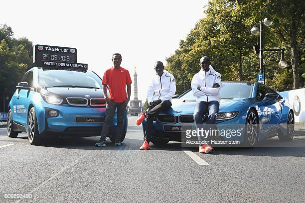 Ethiopia's Kenenisa Bekele former world record holder Wilson Kipsang of Kenya and Emmanuel Mutai of Kenya poses in front of the BMW i3 and BMW i8 at...